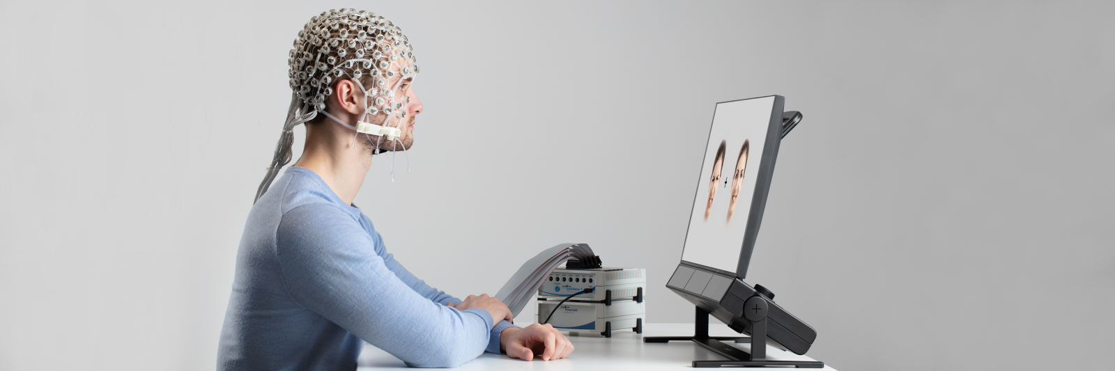 A man using EEG cap looking at Tobii Pro Spectrum