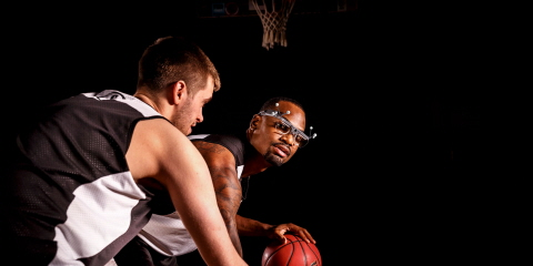 A basketball player wearing Tobii Pro Glasses 2 with reflective markers for motion capture from Qualisys