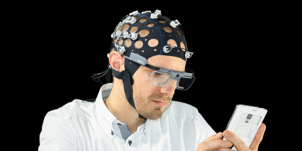 Model wearing EEG cap and Tobii Pro Glasses 2 using a mobile device.