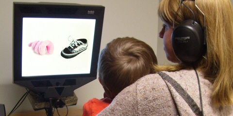 A toddler sitting on his mom's lap watches the  disfluency study movie on the Tobii Pro screen based eye tracker.