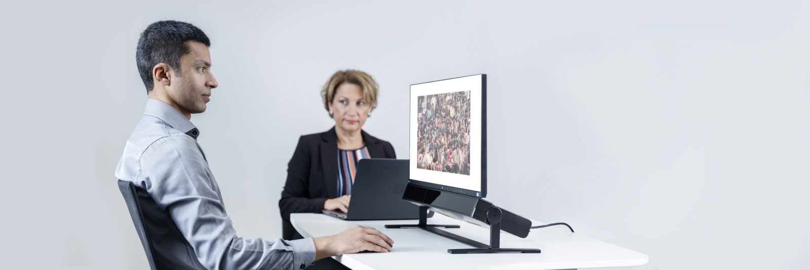 A test participant looks at Tobii Pro Spectrum eye tracker with face recognition stimulus