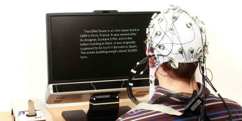 A person wearing bio-metric censors reads a text on the Tobii Pro TX-300 eye tracker screen.