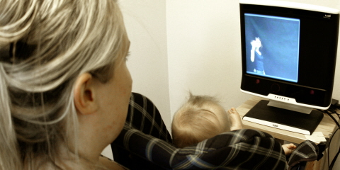 An infant in front of a Tobii ProT120 Eye Tracker  at the Babylab at Uppsala University.
