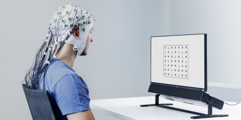 A yound man wearing EEG cap looks at a screen of Tobii Pro Spectrum eye tracker