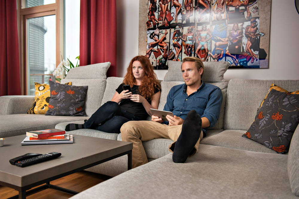 Couple at home looking at tablet, mobile phone and TV