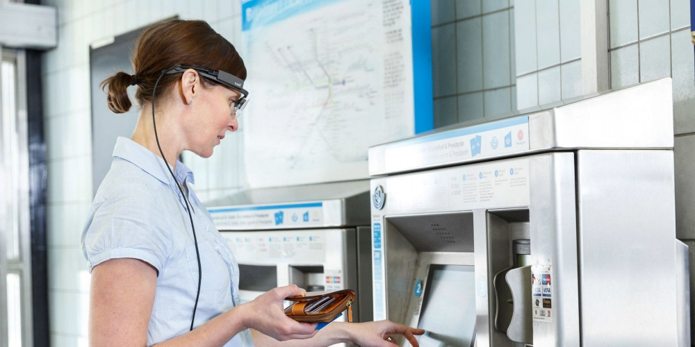 A woman wearing Tobii Pro Glasses 2 buys tickets from a ticket machine.