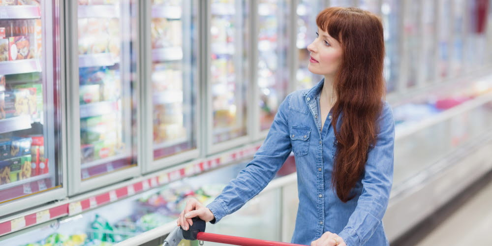 Woman shopping in a grocery store - focus on products