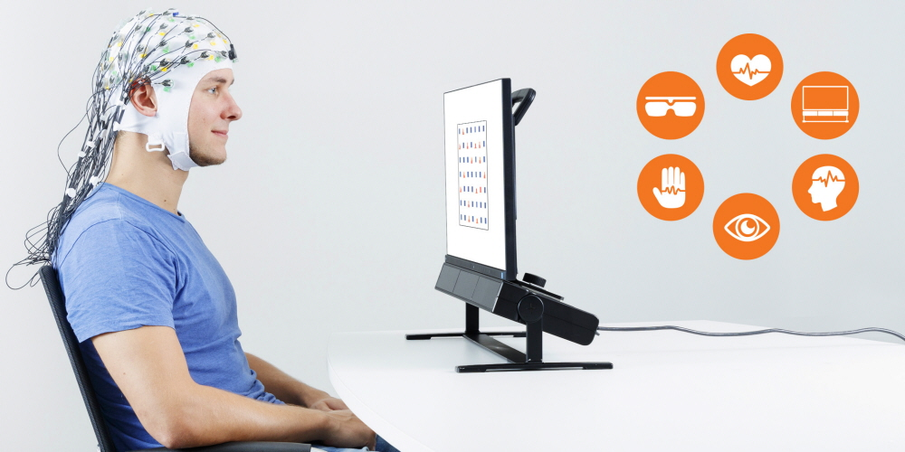 A person wearing EEG cap in front of the Tobii Pro Spectrum eye tracker