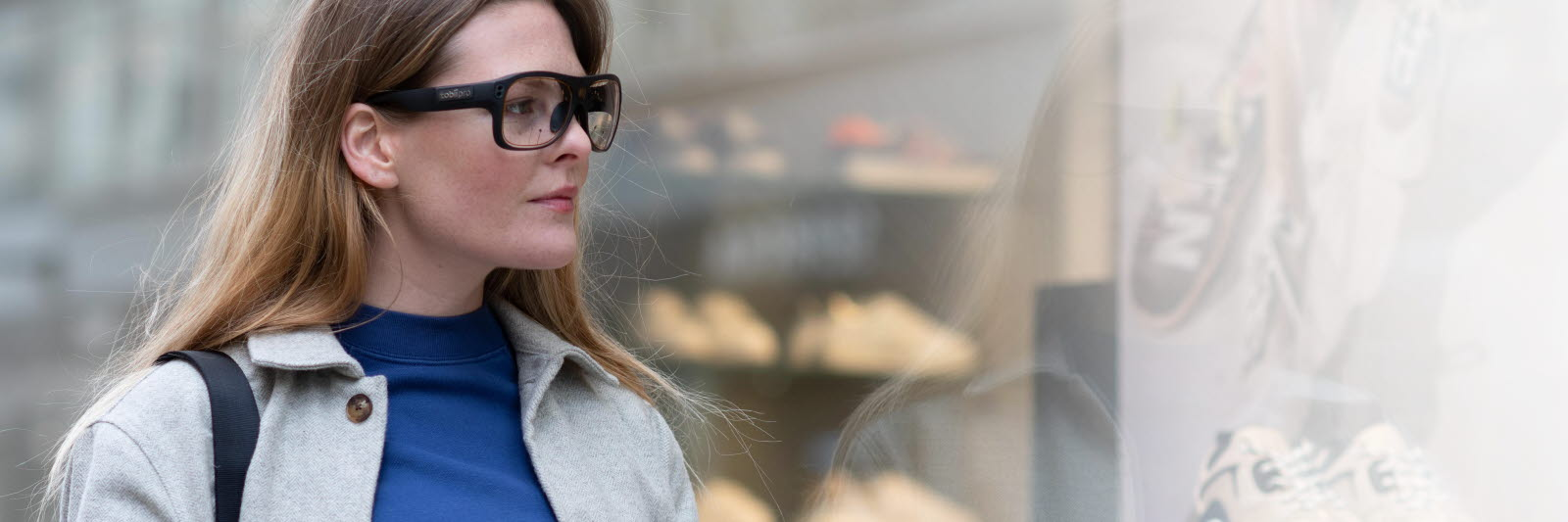 Woman using Tobii Pro Glasses 3 to look at products in a store window
