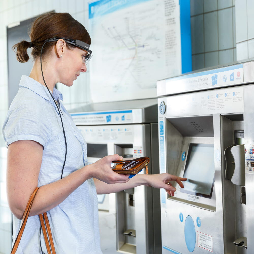Woman using a ticket dispenser using Tobii Pro Glasses 2