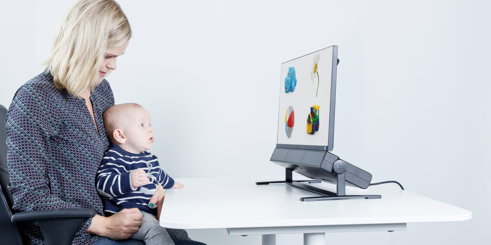 Woman holding a baby using an eye tracker for child development