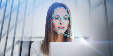 Woman looking at a computer emotion recognition