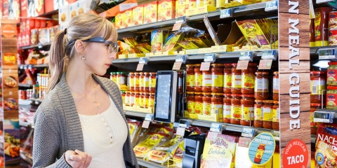 A woman wearing Tobii Pro Glasses 2 looks at a shelf with products.